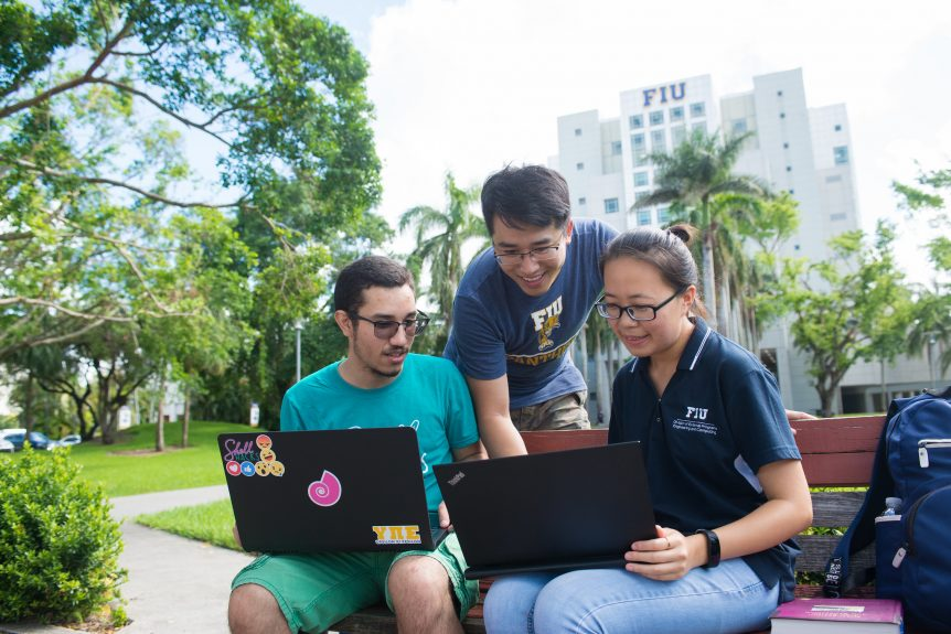 FIU students on campus with laptops